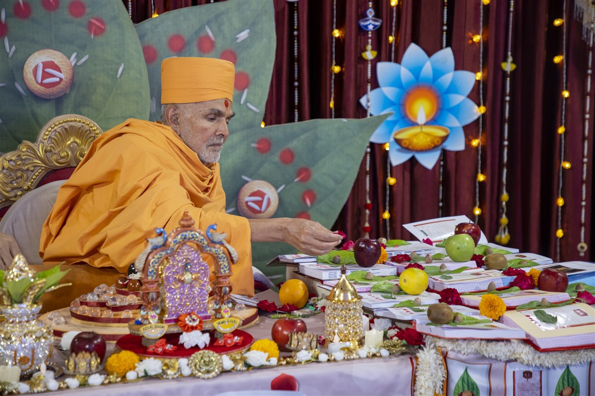 Swamishri places sanctified flowers on account books