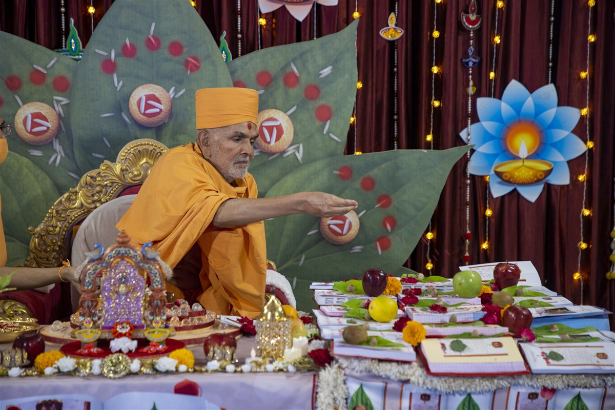 Swamishri showers sanctified rice grains on account books
