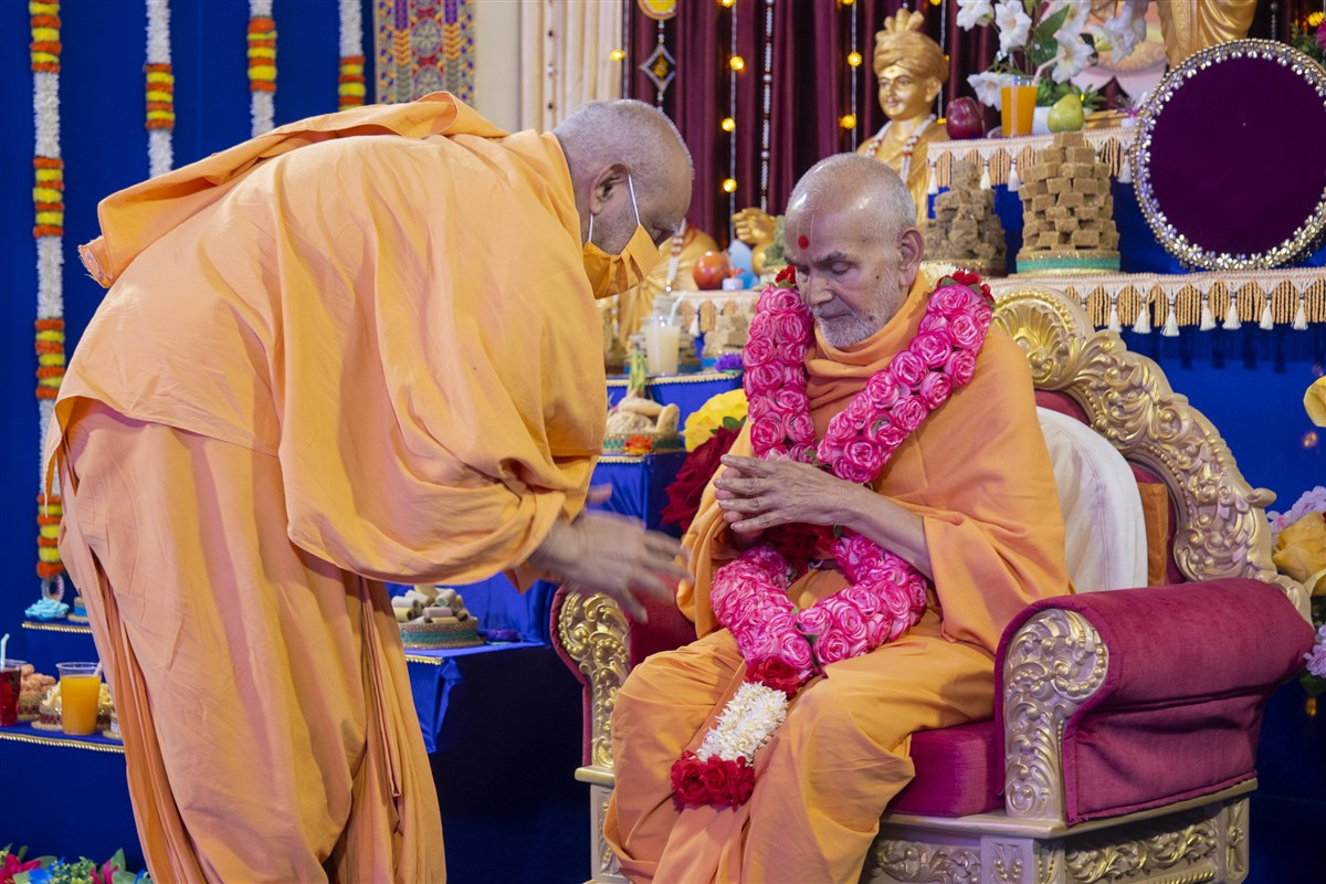 Atmaswarup Swami honors Swamishri with a garland