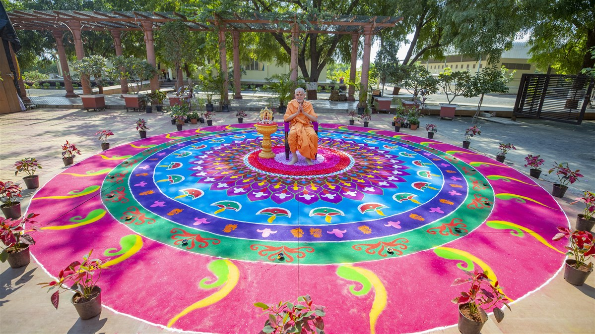 Swamishri seated in the middle of the rangoli design
