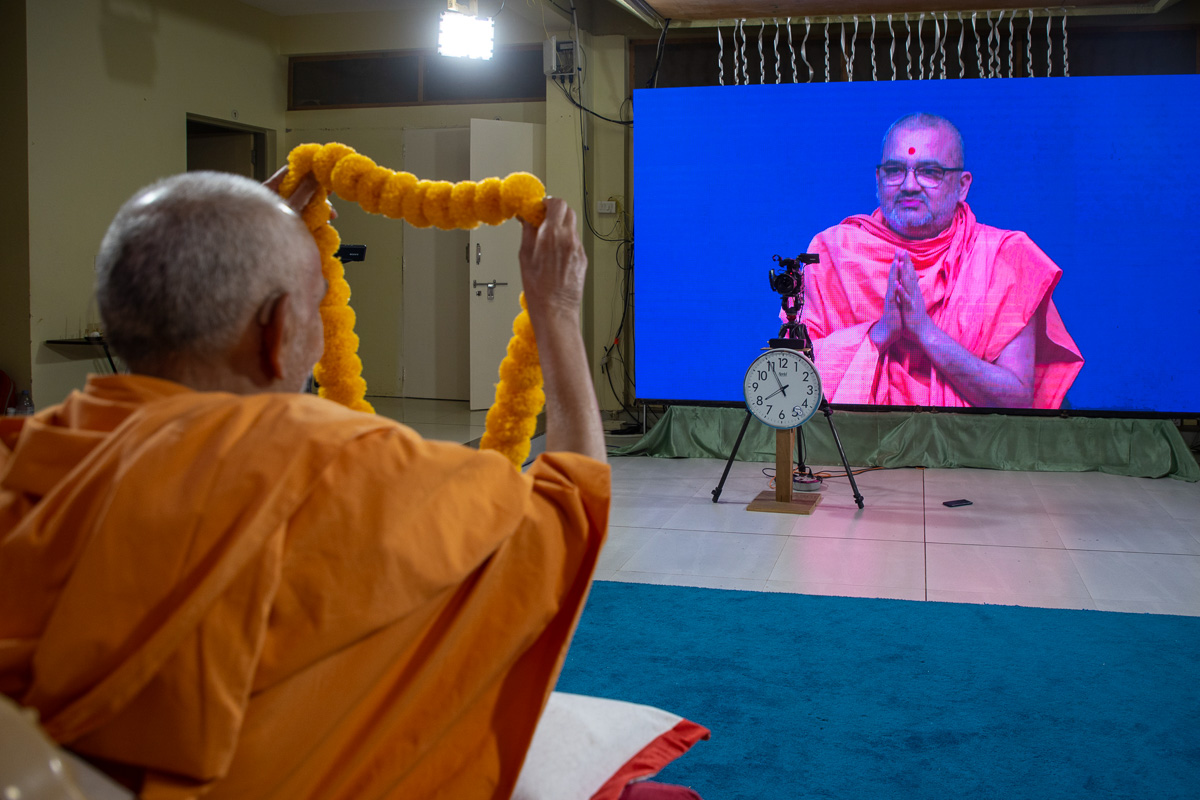 Swamishri honors Bhadresh Swami with a garland