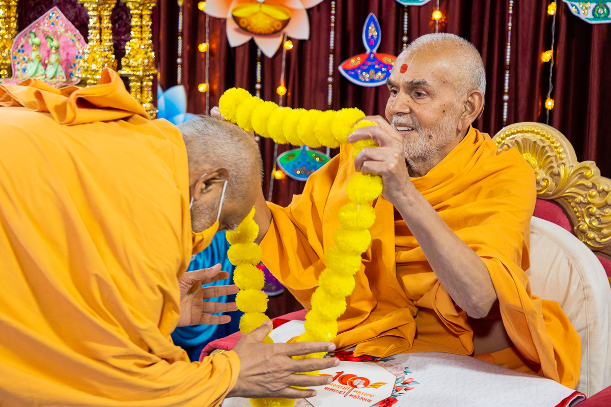 Swamishri honors Atmaswarup Swami with a garland