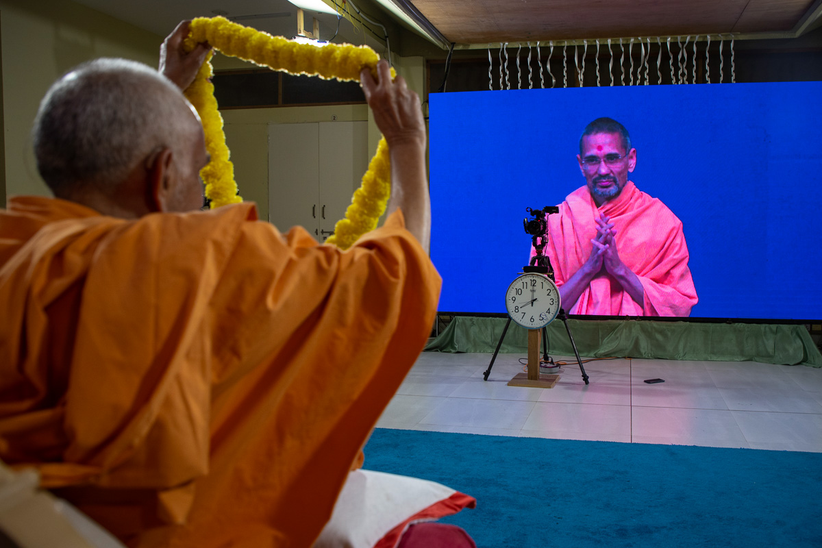Swamishri honors Atmatrupt Swami with a garland