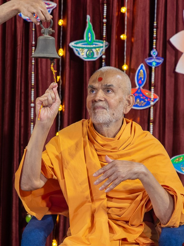 Swamishri rings a bell in honor of the Akshar-Purushottam Darshan