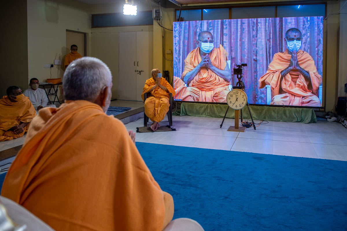 Swamishri greets Pujya Ishwarcharan Swami and Anandswarup Swami with 'Jai Swaminarayan' via video conference