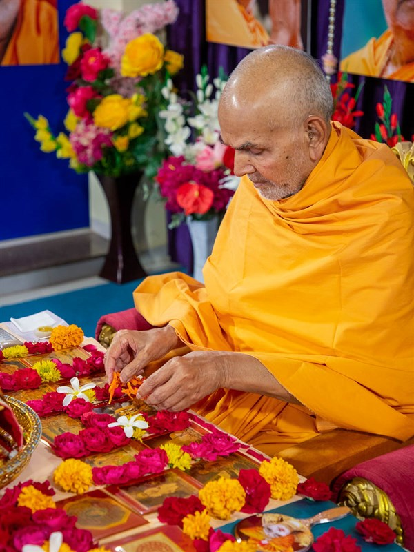 Swamishri adjusts the flowers in his daily puja