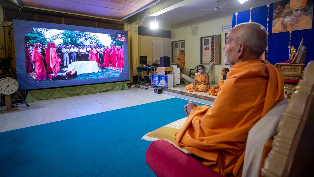 Swamishri watches a video on Pramukh Swami Maharaj