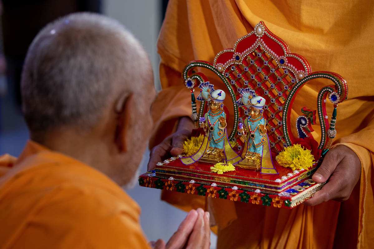 Swamishri engrossed in darshan of Shri Harikrishna Maharaj and Shri Gunatitanand Swami