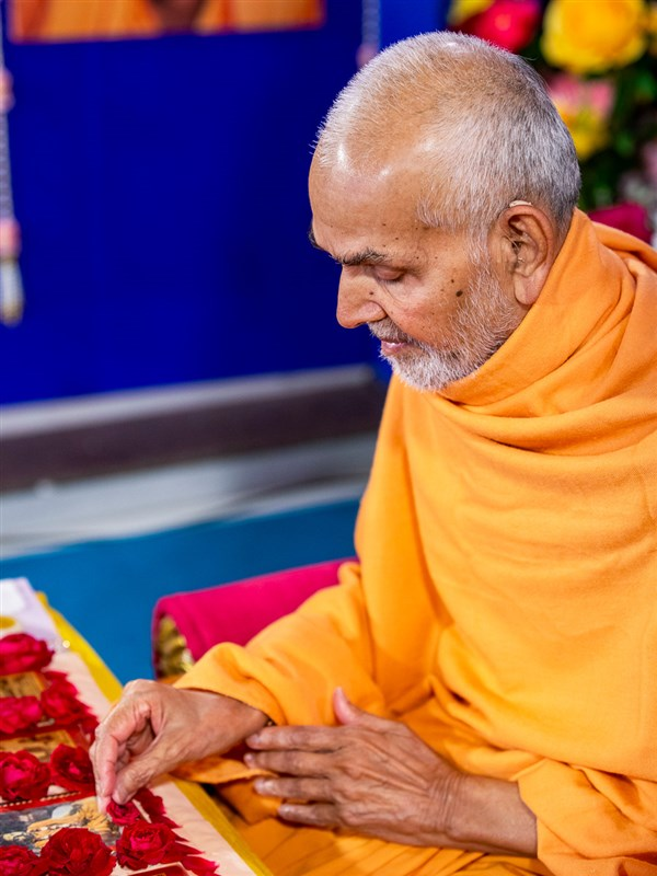 Swamishri adjusts flowers in his daily puja