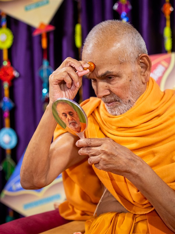 Swamishri applies a chandlo on his forehead