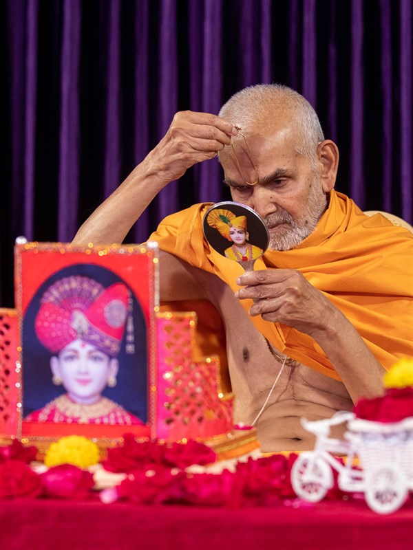 Swamishri applies a tilak on his forehead