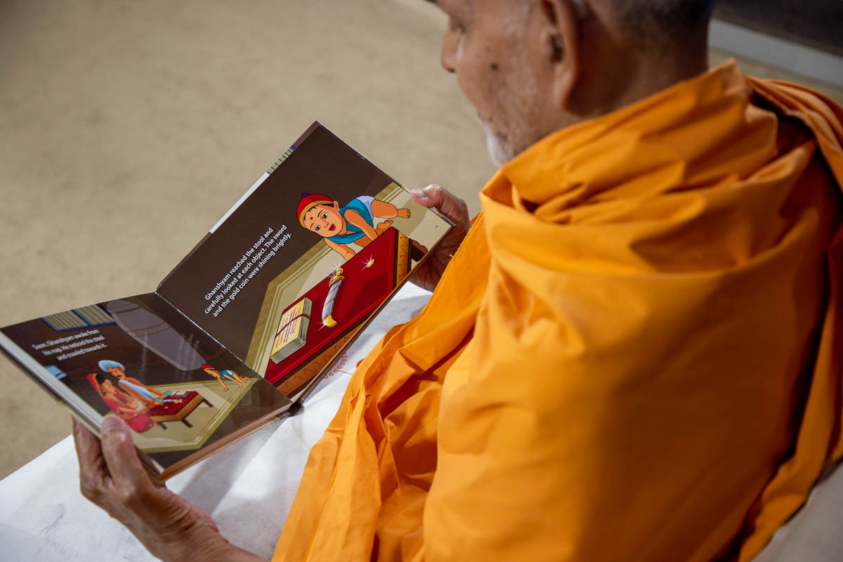 Swamishri looks through the new book