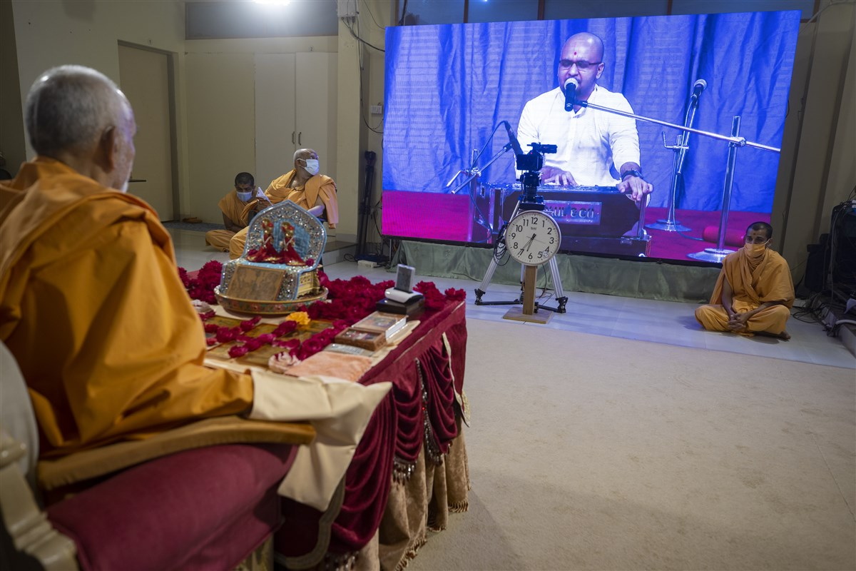A youth sings a kirtan via video conference from Surat Mandir