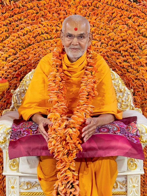 Swamishri honored with a garland made with kesuda flowers