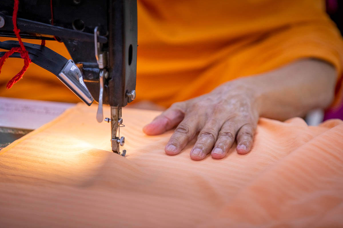 Swamishri operates a sewing machine