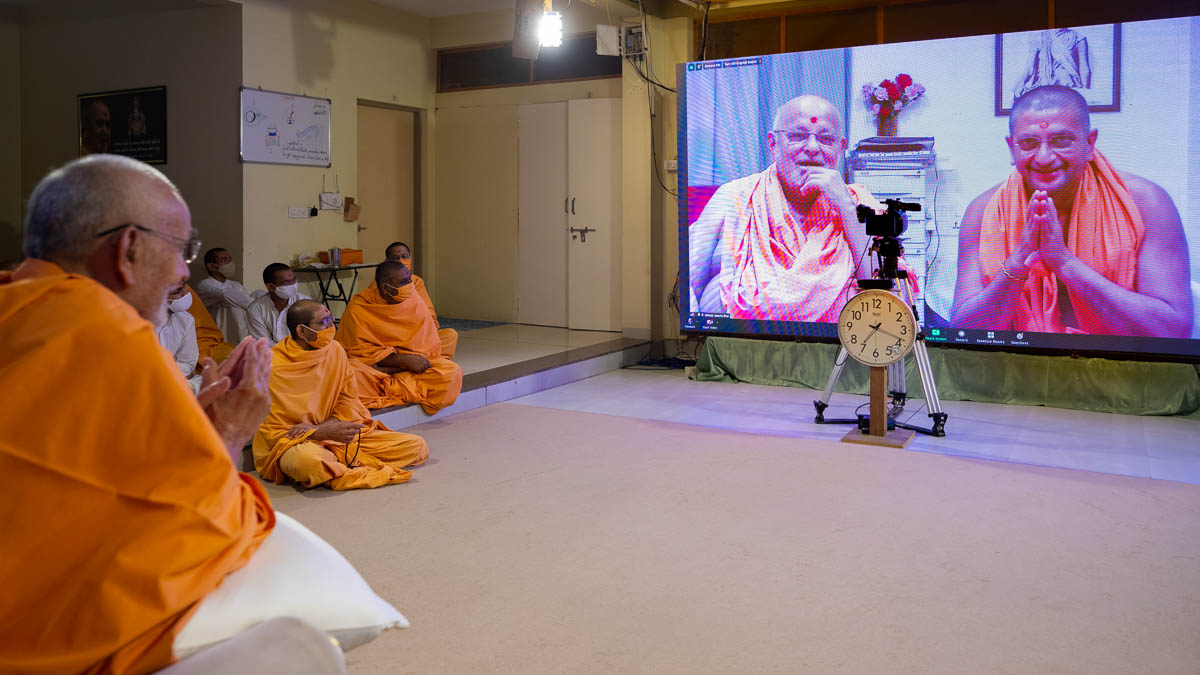 Pujya Ishwarcharan Swami and Rahul Swami doing darshan of Swamishri via video conference