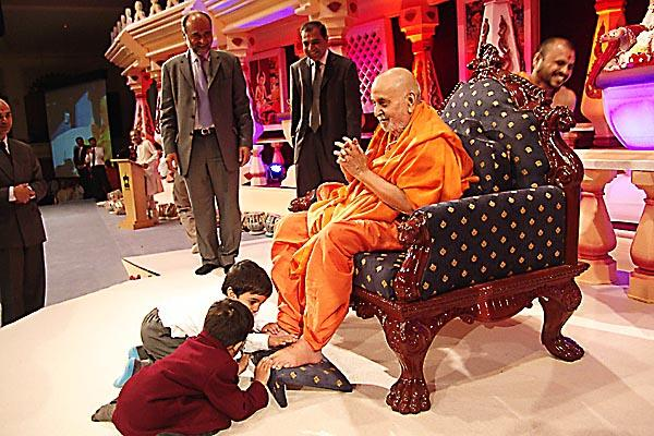 Swamishri being welcomed by two young students