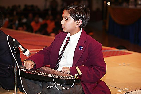 A student demonstrates his learning of Indian classical instruments