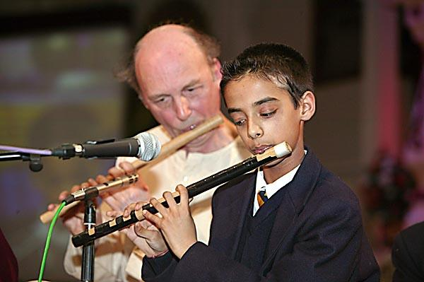A student charms the devotees with his flute playing