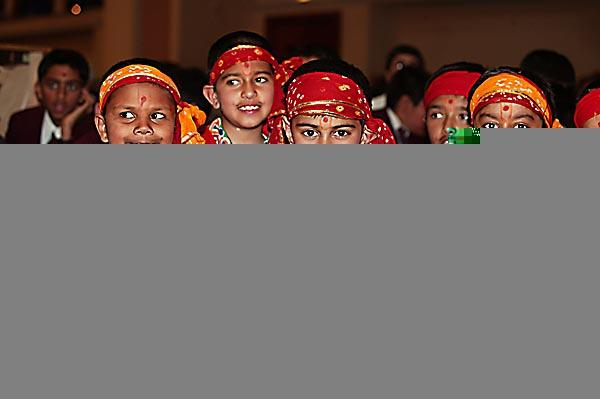 Students dressed in colourful costumes await Swamishri's arrival
