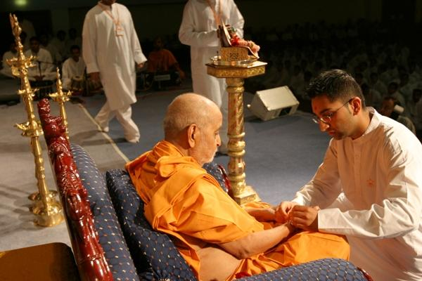 Day 1 - National Kishore-Kishori Summer Shibir  - A  kishore tying a nada chaddi to Swamishri as part of the opening ceremony