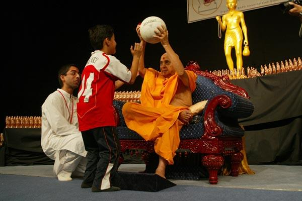 Day 2 - National Bal-Balika Shibir 2004  - Swamishri plays with a balak at the launch of the Pramukh Cup