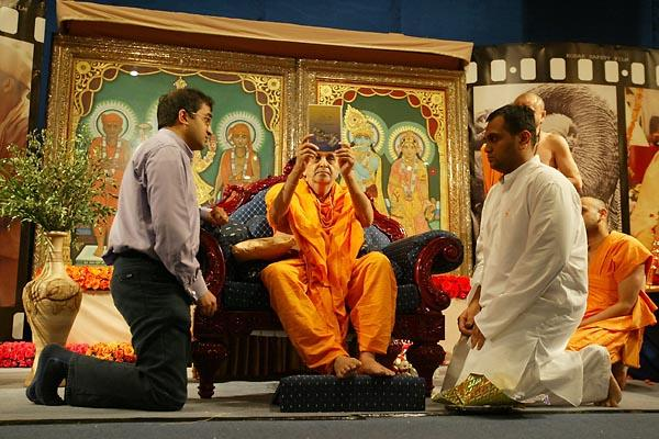 Janmasthami and London Mandir Patotsav Ceremony  -  Swamishri opens the newly-released Sahaj Anand DVD