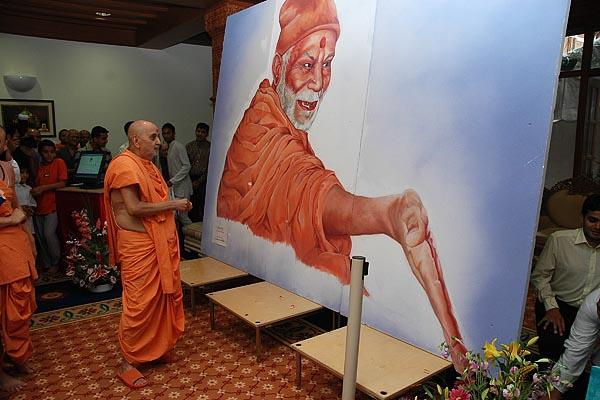 Janmasthami and London Mandir Patotsav Ceremony  - Swamishri admiring the picture of Yogiji Maharaj painted by two kishoris