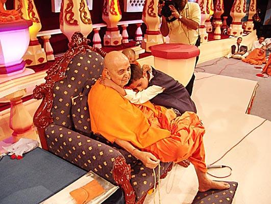 A young child shows his love for Swamishri