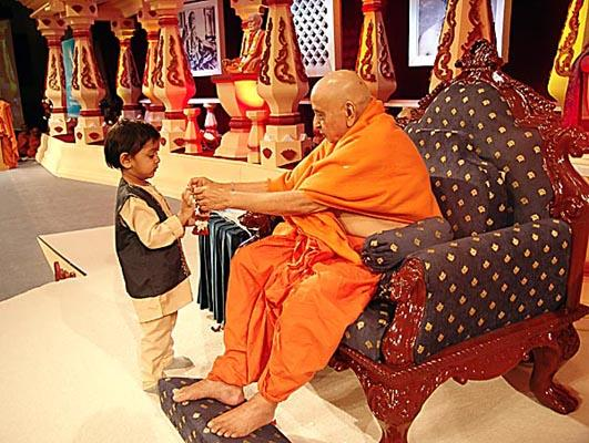 Swamishri gives a small garland to a child who wandered onto the stage