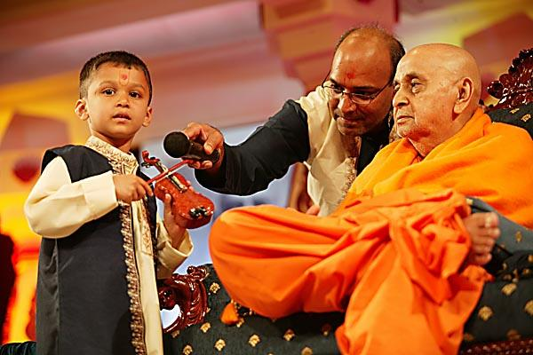 Swamishri asks the child to play the mini violin
