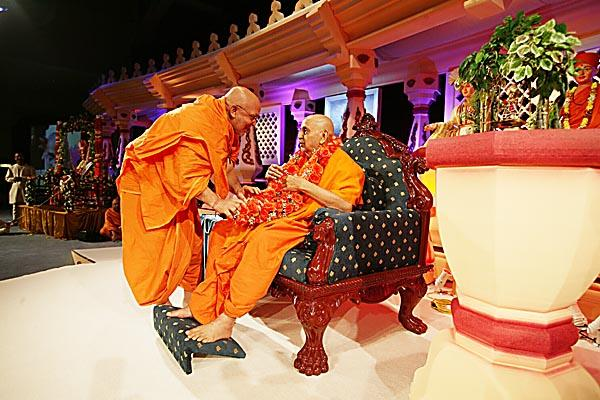 Ghanshyamcharan Swami welcomes Swamishri with an orange rose garland