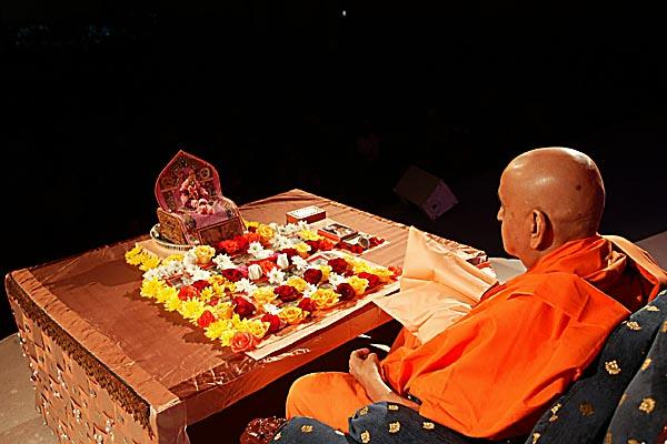 Swamishri turning the rosary in pooja