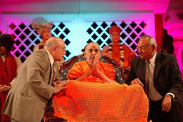 Members of the Board of Trustees place a shawl on Swamishri