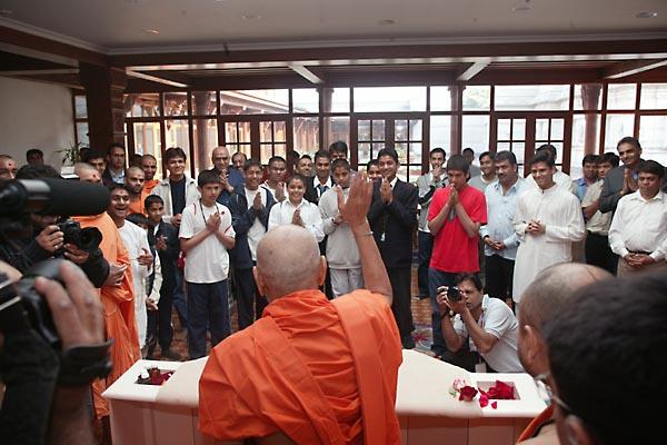 Swamishri raises his hand in blessing to children who pledged not to watch films or TV