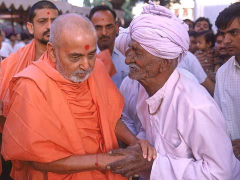 Listening attentively to a tale of sorrow and pain from an old blind devotee...
