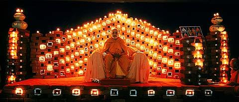 Swamishri during the evening welcome assembly, with a village backdrop of bricks and lamps illuminating the stage .