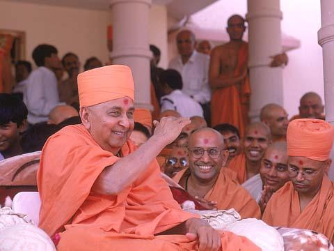 Swamishri in a joyous mood after arriving to the Rajkot mandir from Mumbai at 3:35 pm. Swamishri blesses a throng of 400 devotees who had been avidly waiting for Swamishri's darshan for several hours. 23 Oct 99
