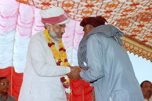A Muslim villager garlands the Chief Minister