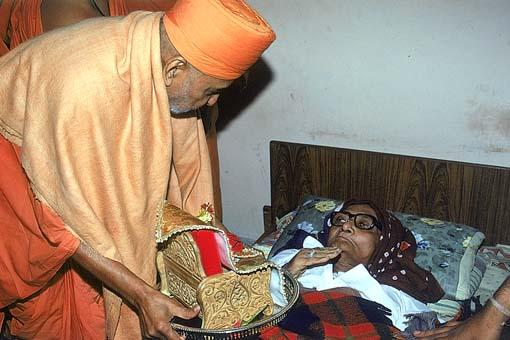 Blessing an ailing devotee with the darshan of Harikrishna Maharaj