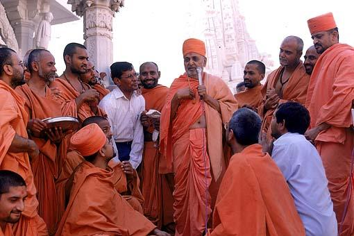 Calmly sharing words of wisdom and humor to an audience of sadhus and devotees