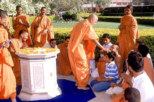 Before the shrine where Shastriji Maharaj's mortal body was placed prior to cremation, Swamishri blesses a young boy by placing a flower on his head