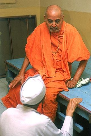 Swamishri casually sits on an ordinary platform and discusses and gives guidance to a few devotees on a personal matter