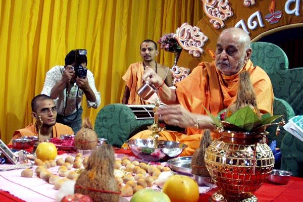 Swamishri bathes deities with water