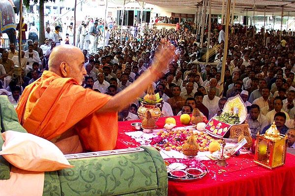 Swamishri blesses the devotees by showering rice grains (ashirvad)
