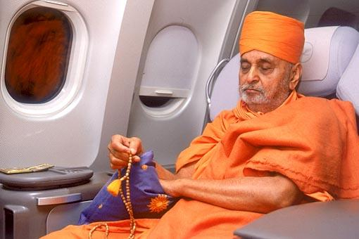 Engrossed in bhajan during the flight to Muscat