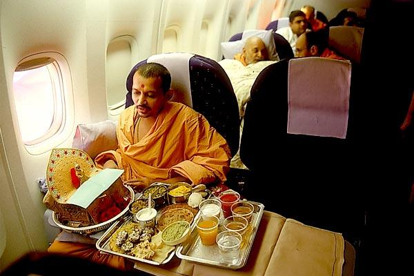 On the flight from Singapore to Perth thal is offered to Shri Harikrishna Maharaj. Swamishri is in the seat behind