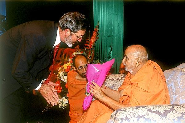 Deputy Chief Executive Officer of City of Sterling(Perth), Mr. R.A. Constantine, greets Swamishri with a bouquet during a public assembly