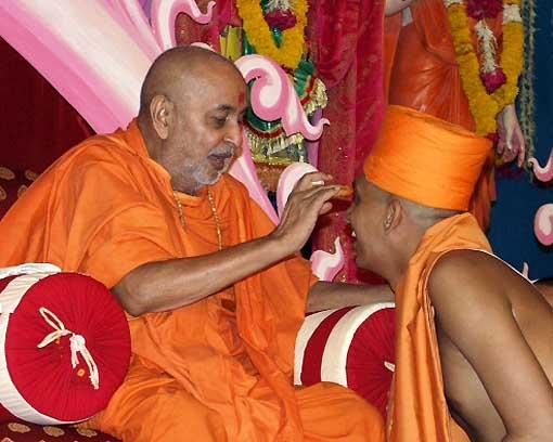 Swamishri applies chandan and blesses the newly initiated sadhu