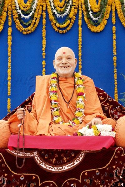The animatronic murti of Yogiji Maharaj sways, tells the rosary and raises its left hand to bless